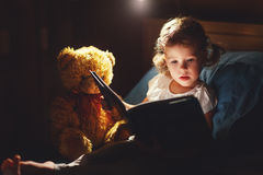 child-girl-reading-book-bed-going-to-sleep-87310824